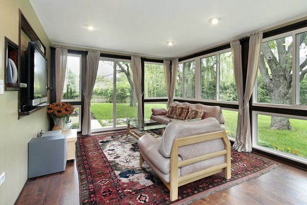 In-floor heating or rugs add warmth to a sunroom and help define the space.