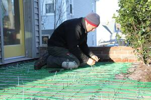 A Concord Carpenter, Rob Robillard, installas a WarmlyYours snow melting system in a wheelchair ramp for Massachusetts homeowner Rob Butts.