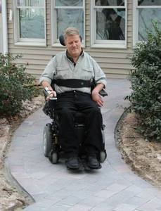 A heated outdoor pathway aids a handicapped homeowner.